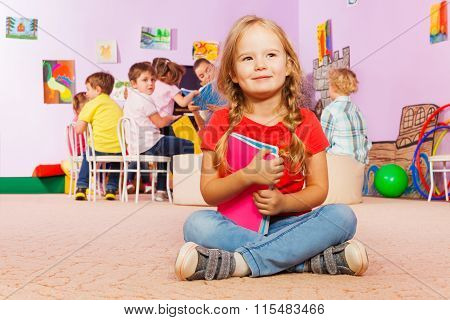 Portrait of little girl with books in class