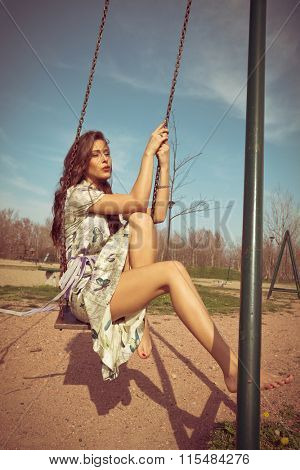 barefoot young woman sit on swing in summer dress  full body shot, wind in hair, retro colors