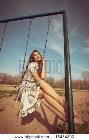 barefoot young woman sit on swing in summer dress  full body shot, retro colors