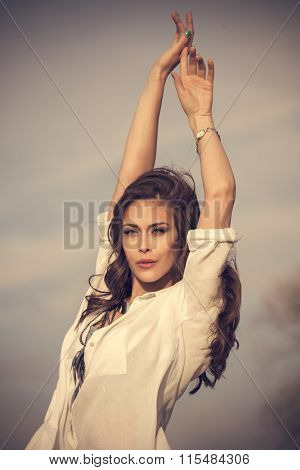 young woman in white shirt  with arms up stand in wind, natural light, outdoor summer day