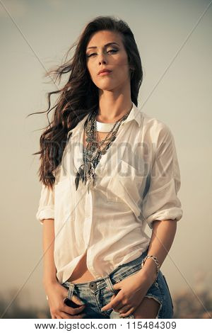 summer fashion young woman in white shirt and metal necklace portrait, stand in wind, natural light, outdoor