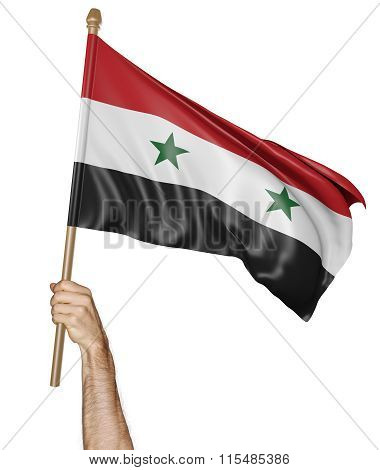 Hand proudly waving the national flag of Syria