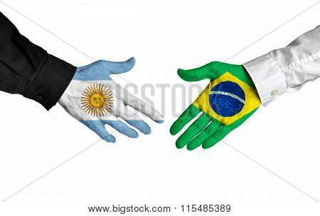 Argentina and Brazil leaders shaking hands on a deal agreement