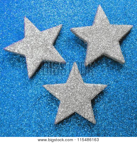 Three Large Silver Stars On Bright Blue Glittery Background