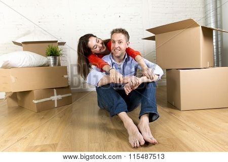 Young Happy Couple Sitting On Floor Together Celebrating Moving In New Flat House Or Apartment