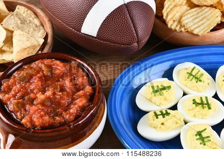 Closeup of snacks for watching a football game, chips, salsa and deviled eggs. Great for Super Bowl or Playoff themed projects.