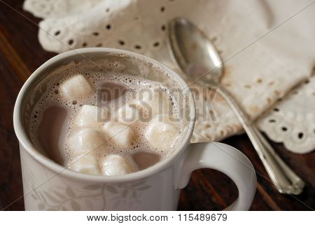 Hot chocolate with melting marshmallows on rustic table with vintage spoon and antique lace napkin.  Closeup with shallow dof.  Selective focus on marshmallows.