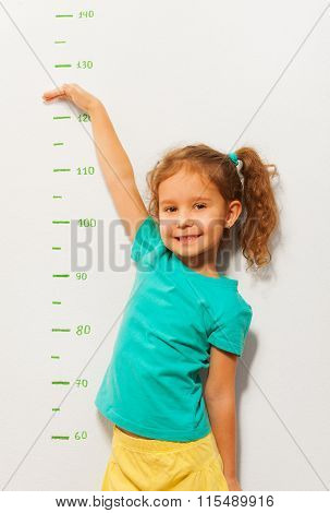 Little girl show her height on a scale drawn on the wall with hand and smile on face