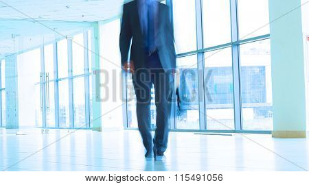 Businessman walking in the corridor of an business center
