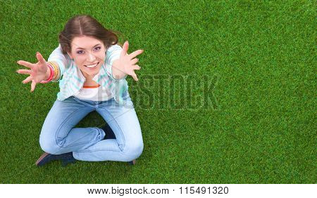 Top view of beautiful young woman sitting on the green grass