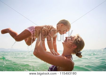 Closeup Mother Teaches Swim Small Daughter In Azure Sea