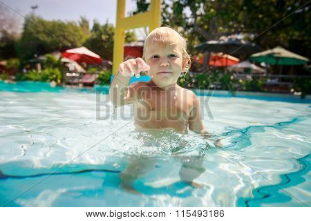 Small Blonde Girl Stands Looks In Transparent Water Of Pool