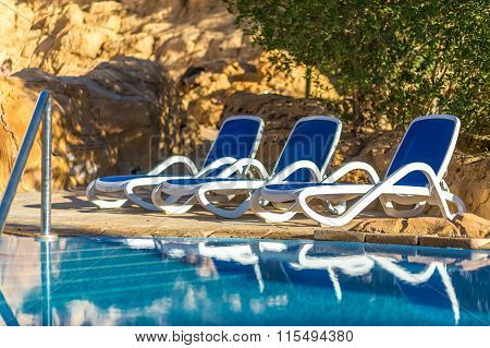 Several of sun loungers by beautiful swimming pool and treess.