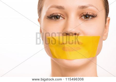 Young girl with her mouth taped.