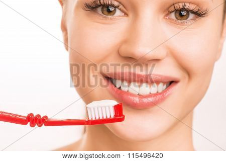 Young girl upholding a toothbrush.