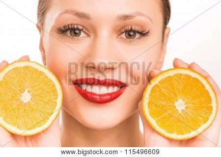 Young smiling girl with two halves of orange.