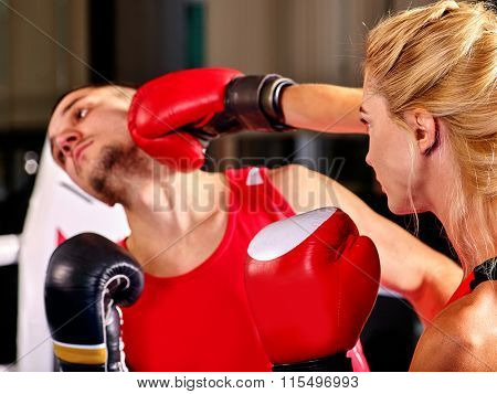 Couple wearing gloves Boxing in Ring. Woman knocks  man in jaw.