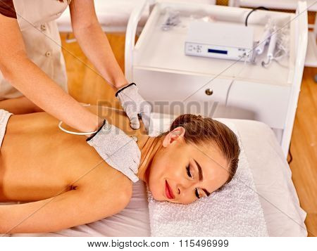 Woman  receiving electric body massage by hardware cosmetology. Beautician wearing electricity gloves.