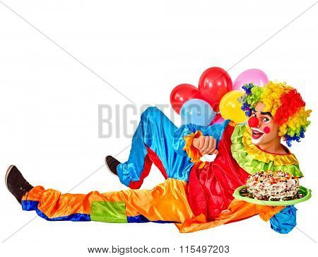 Happy birthday clown holding cakes and bunch of balloons lying on floor.  Isolated.