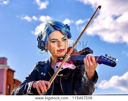 Girl violinist with blue hair playing  aganist sky with clouds outdoor.