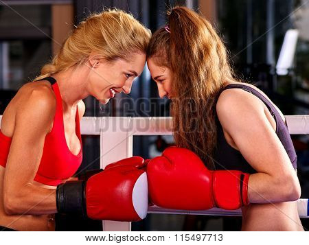 Two  friendly women boxer wearing red  gloves to box in ring.