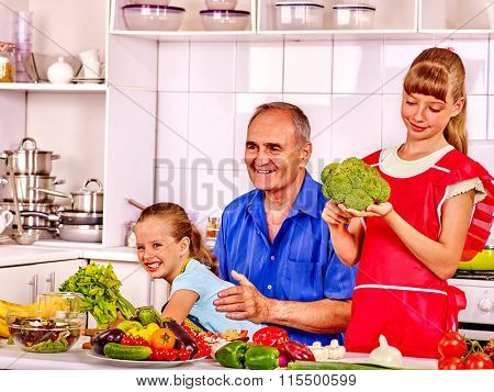 Grandfather  with her children cooking at kitchen.