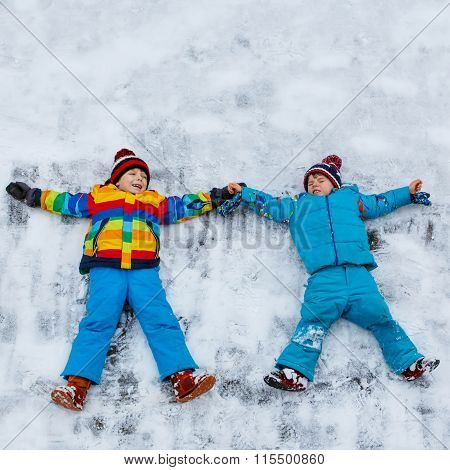 Two little kid boys making snow angel in winter, outdoors