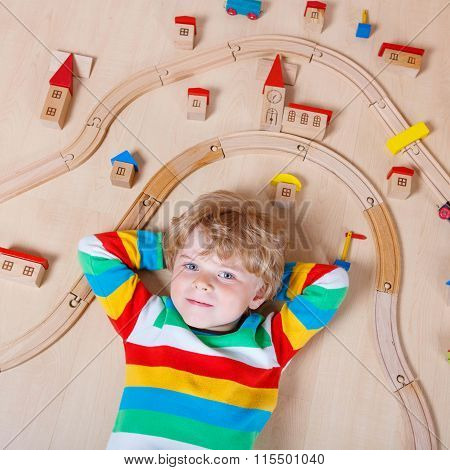 Little blond child playing with wooden railroad indoor