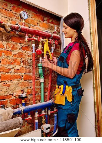 Plumber woman  builder fixing heating system with special tool.