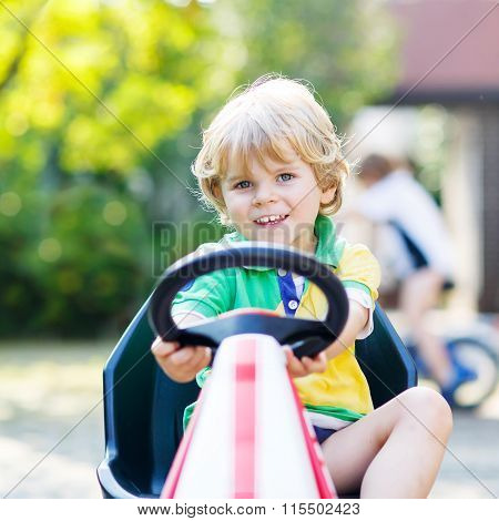 Little kid boy driving pedal car in summer garden