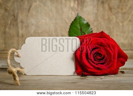 Red Rose With Empty Tag For Your Text On Wooden Background