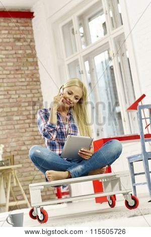 Attractive young woman sitting in retro home, talking on mobilephone using tablet computer.