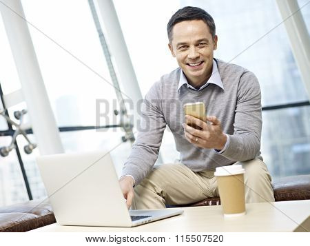 Man Using Cellphone And Laptop