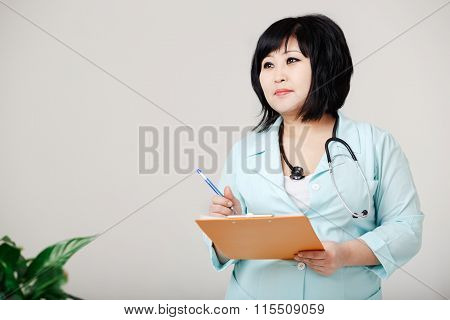 Curvy female nurse stands still writes the results by pen at paper, in medical lab coat with stethos