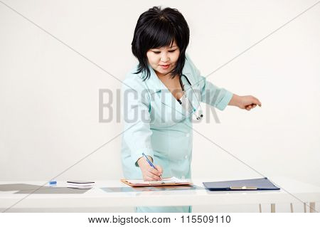 Cute curvy female doctor standing at her desk writes results of survey on paper by pen, medical lab