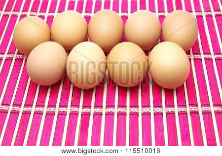 Eggs on pink bamboo mat. Focus on head of eggs of back row.