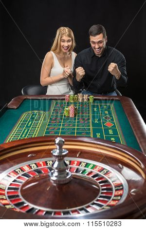 Man and woman cheering at roulette table in casino