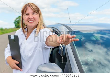 Portrait Of A Woman Near The Car. Keys In His Hand In Focus