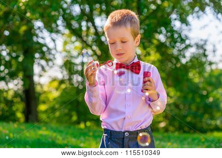 A Boy In A Green Park Blowing Soap Bubbles