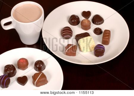 Top View Of Two Plates Of Chocolates With A Cup Of Hot Chocolate