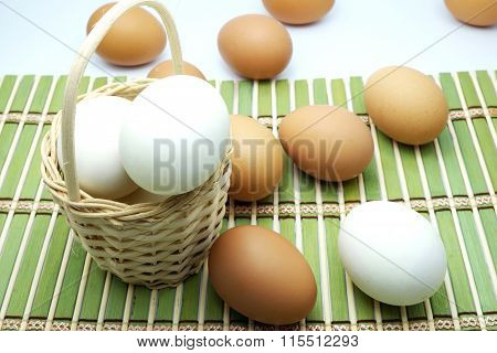 Brown and white eggs in/around wooden basket on green bamboo mat.