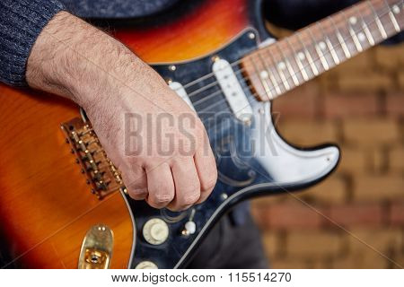 Hand Of Guitar Player Turning Knobs On An Electric Guitar