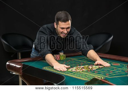 Young handsome man playing roulette wins at the casino
