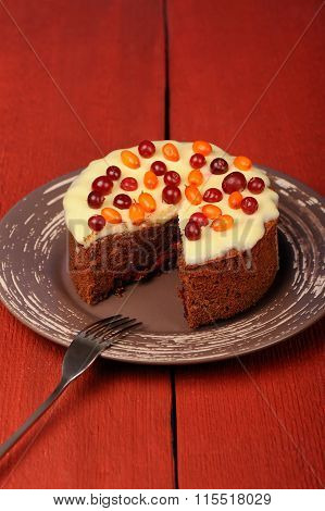 Homemade Chocolate Cake With Fresh Cranberries, Sea-buckthorn And Icing On Red Table