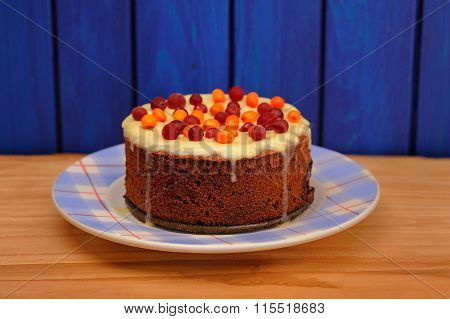 Homemade Tasty Chocolate Cake With Fresh Cranberries, Sea-buckthorn And Icing On Wooden Background
