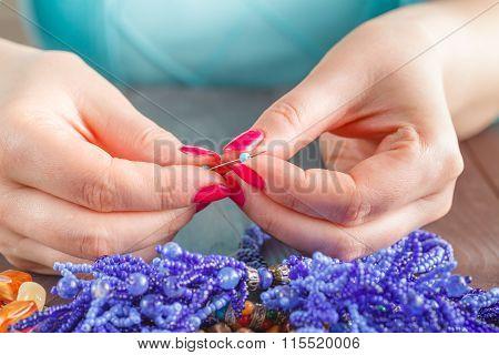 Woman Stringing Beads