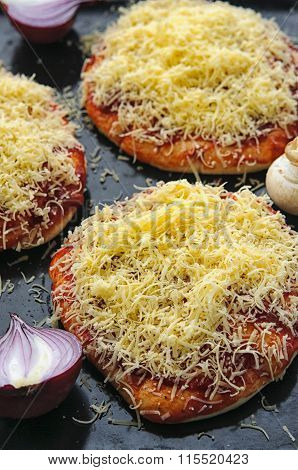 Mini Pizzas Or Small Pellets Covered With Cheese On Black Glance Surface Close-up Macro
