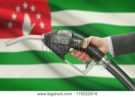 Fuel Pump Nozzle In Hand With National Flag On Background - Abkhazia