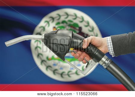Fuel Pump Nozzle In Hand With National Flag On Background - Belize