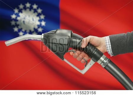 Fuel Pump Nozzle In Hand With National Flag On Background - Burma